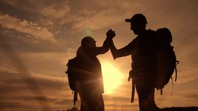 Teamwork business journey concept win. team tourists man and woman sunset silhouette help shake hands success victory stock footage