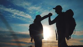 Teamwork business journey concept win. Team tourists man and woman sunset silhouette help shake hands success victory stock video