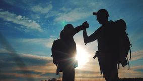 Teamwork business journey concept win. team tourists man and woman sunset silhouette help shake hands success victory stock video footage