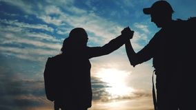 Teamwork business journey concept win. Team tourists man and woman sunset silhouette help shake hands victory success stock video