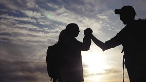 Teamwork business journey concept win. team tourists man and woman sunset silhouette help shake hands victory success. Slow motion video. tourism husband and stock footage