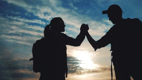 Teamwork business journey concept win. Team tourists man and woman sunset silhouette help shake hands victory success stock footage