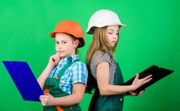 Teamwork business.. Labor day. 1 may. Little kid in helmet with tablet. Foreman inspector. Repair. small girls repairing. Together in workshop. Discussing some royalty free stock image