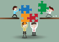 Teamwork, business men assembling pieces of a puzzle Stock Photography