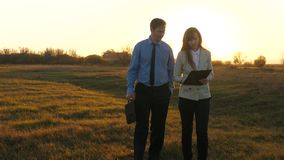 Teamwork of business partners in the sunset light. Slow motion. businessman with a briefcase and business woman business