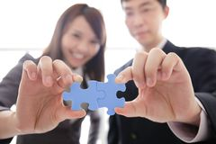 Teamwork. Business people assembling jigsaw puzzle, asian Royalty Free Stock Photo