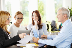 Teamwork. Business people discussing financial plans and working on laptop and tablet. Teamwork Stock Photos