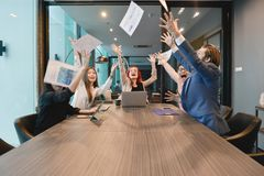 Teamwork of business people excited, business documents fly in a. Ir, multi ethnics Royalty Free Stock Photo