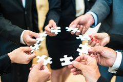 Teamwork - Business people solving a puzzle stock photography