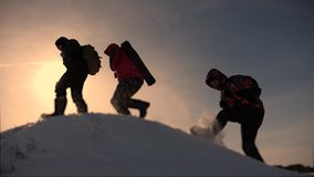 Teamwork of business people. three climbers climb one after another on a snow-covered hill. team of business people go. Teamwork of business people. three stock video footage