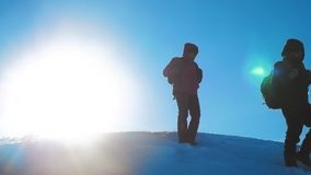 Teamwork business winter adventure. Men tourists climbing walking top mountains rocks peak group team sunlight. Silhouette on snow feet winter snow trip. Slow stock video footage