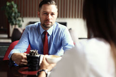 Teamwork. Businessman and businesswoman sitting at table in coffee shop and discuss business plan. On table is laptop Stock Image