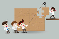 Teamwork, businessmen assembling pieces of a puzzle Stock Images