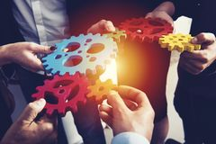 Business team connect pieces of gears. Teamwork, partnership and integration concept. Teamwork of businesspeople work together and combine pieces of gears royalty free stock image