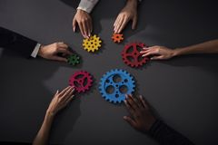 Business team connect pieces of gears. Teamwork, partnership and integration concept. Teamwork of businesspeople work together and combine pieces of gears stock photo
