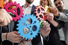 Business team connect pieces of gears. Teamwork, partnership and integration concept. Teamwork of businesspeople work together and combine pieces of gears royalty free stock photography
