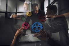 Business team connect pieces of gears. Teamwork, partnership and integration concept. Double exposure. Teamwork of businesspeople work together and combine royalty free stock image