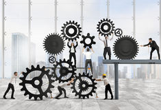 Teamwork of businesspeople. Work together to a system of gears Royalty Free Stock Images