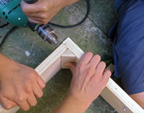Teamwork - carpentry. Helping to make wooden cabinet. Drilling a hole in lumber royalty free stock images