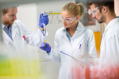 Teamwork in chemical lab put sample of liquid in test pipette Stock Photo