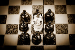 Teamwork with chess pawn checkmating opposing King, sepia version, Stock Photo