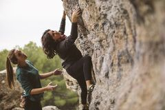 Teamwork of climbers. Two women climbers. Teamwork of climbers. Two women climbers helping to climb royalty free stock photos