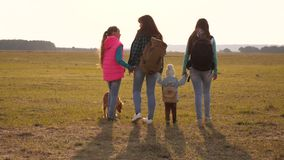 Teamwork of a close-knit family. family travels with the dog across the plains and mountains. mother, daughters and home. Teamwork of close-knit family. family stock footage