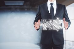 Teamwork and collaboration concept. Businessman holding creative puzzle sketch on blurry interior background. Teamwork and collaboration concept. 3D Rendering Royalty Free Stock Photos