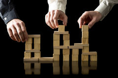 Teamwork and collaboration. Hands of three businessman assembling a balanced and stable structure of wooden cubes on a black desk with reflection and black Royalty Free Stock Images