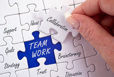 Teamwork and collaboration. Jigsaw puzzle with text 'team work' in uppercase white letters under the position of a white missing piece marked 'collaboration' Royalty Free Stock Photos