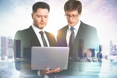 Teamwork and communication concept. Two handsome european businessmen using laptop together on blurry city background. Teamwork and communication concept. Double royalty free stock images