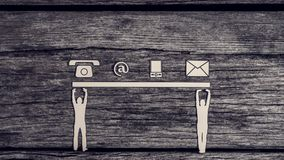 Teamwork and communications concept. With cut outs of two men supporting a line of phone, web and mail icons from below over a rustic textured wood background Royalty Free Stock Image