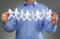 Teamwork. Community and support concept with businessman holding paper chain group of people holding hands Royalty Free Stock Photos