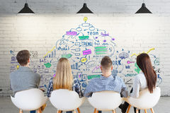 Teamwork concept. Back view of young european team in interior looking at brick wall with business sketch. Teamwork concept Royalty Free Stock Image