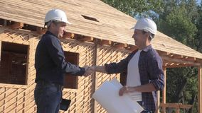 Teamwork. concept building constructing architect slow motion lifestyle video. two men builder in helmets shake hands. Contract business contrast at stock video