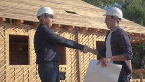 Teamwork. concept building constructing architect slow motion video. Two lifestyle men builder in helmets study digital stock footage