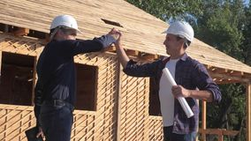 Teamwork. concept building constructing architect slow motion video. two men builder in helmets shake hands contract. Lifestyle business contrast at stock video