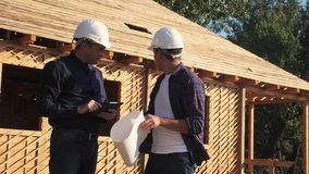 Teamwork. concept building constructing architect slow motion video. two men builder in helmets study the house plan. Two architects working on construction of stock video footage