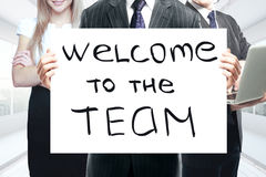 Teamwork concept. Businesspeople holding whiteboard with `welcome to the team` text. Teamwork concept Stock Photography