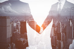 Teamwork concept. Businesspeople shaking hands on modern city background. Teamwork concept. Double exposure Royalty Free Stock Image