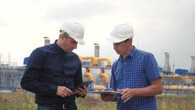 teamwork concept de station de production de gaz d'industrie vid?o anim?e lente deux ingénieurs dans les casques étudient le trav banque de vidéos