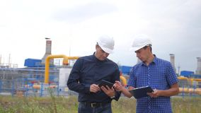teamwork concept de station de production de gaz d'industrie vid?o anim?e lente deux ingénieurs dans les casques étudient le trav clips vidéos