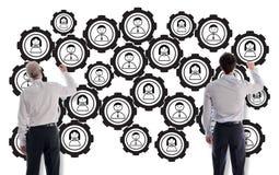 Teamwork concept drawn by businessmen. Teamwork concept drawn on a white wall by businessmen royalty free stock photography