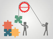 Teamwork concept - an employee raises a puzzles on a rope Stock Photos