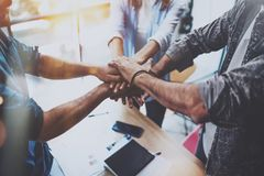 Teamwork concept.Group of three coworkers join hand together during their meeting. Horizontal.Blurred background. stock photography