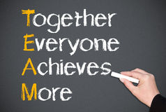 Teamwork concept. Hand of person writing together everyone achieves more on blackboard, teamwork concept Royalty Free Stock Photos
