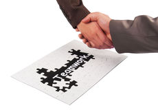 Teamwork concept. Handshaking and puzzle as teamwork concept Stock Images