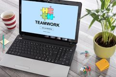 Teamwork concept on a laptop. Laptop on a desk with teamwork concept on the screen stock image