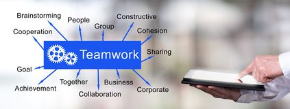 Teamwork concept with man using a tablet. Man using a tablet with teamwork concept stock images