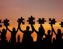 Teamwork concept, silhouette group of people showing jigsaw for connection.  royalty free stock photos